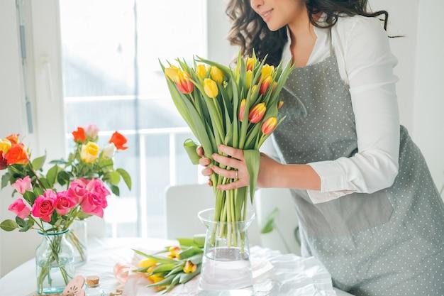 젊은 여성 플로리스트는 꽃의 꽃다발을 수집합니다. 휴가. 선물. 튤립 꽃다발입니다.