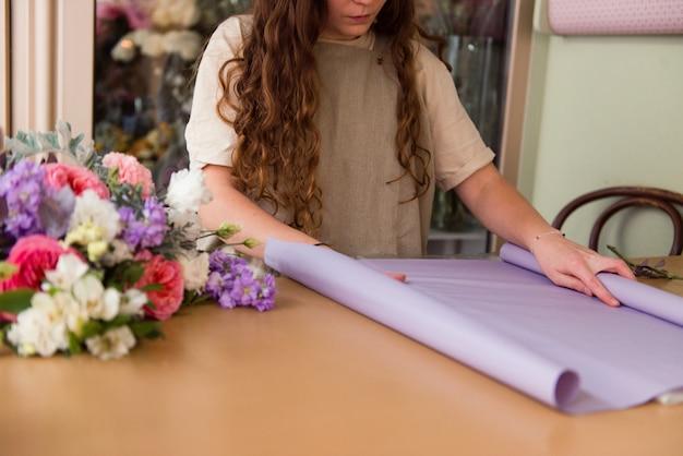 若い女性の花屋は花束のために包装紙をカットします