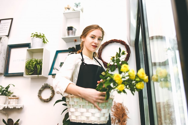 Young woman florist in a flower salon.
