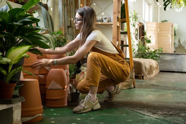 젊은 여성 꽃집 잡고 화분 집 식물 이식