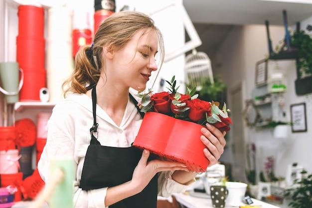 黒のエプロンで若い女性の花屋は花の手帽子ボックスを保持します
