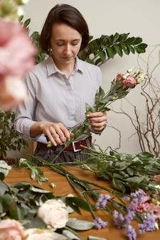 美しい花束を作る彼女のスタジオで若い女性の花屋