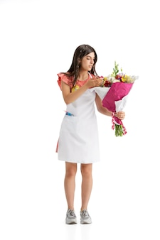 白いスタジオの背景に分離された花束を持つ若い女性の花屋