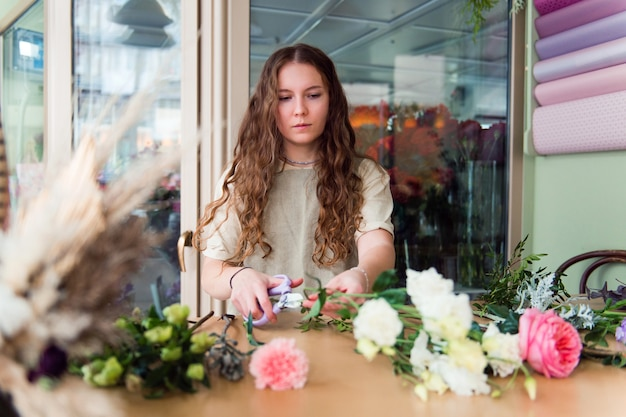 若い女性の花屋は職場で花を扱う中小企業のコンセプトライフスタイルトリミングされた肖像画の花をクローズアップ