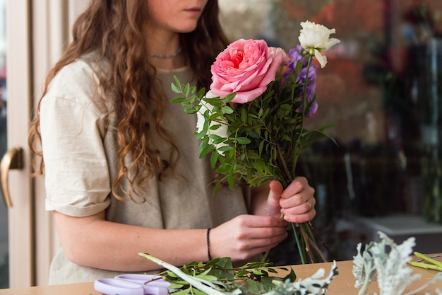 Young woman florist work with flowers at workplace small business concept lifestyle cropped portrait flowers close up