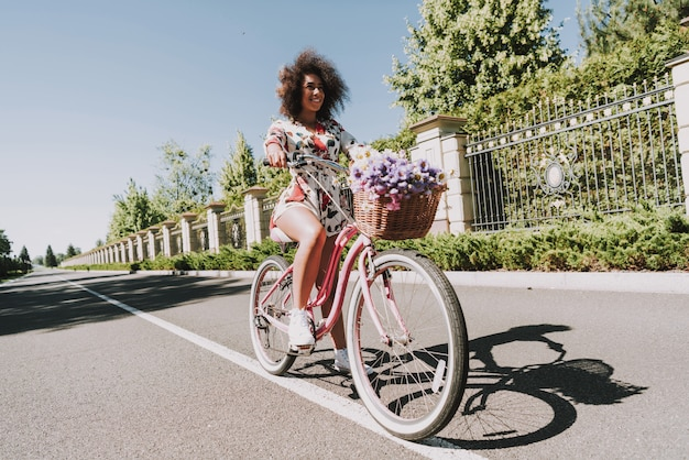 Young woman in flower dress is cycling outside.