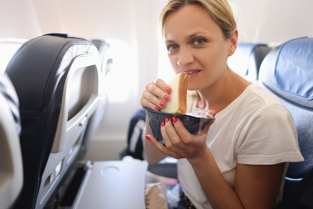 Young woman flying in airplane and eating sandwich