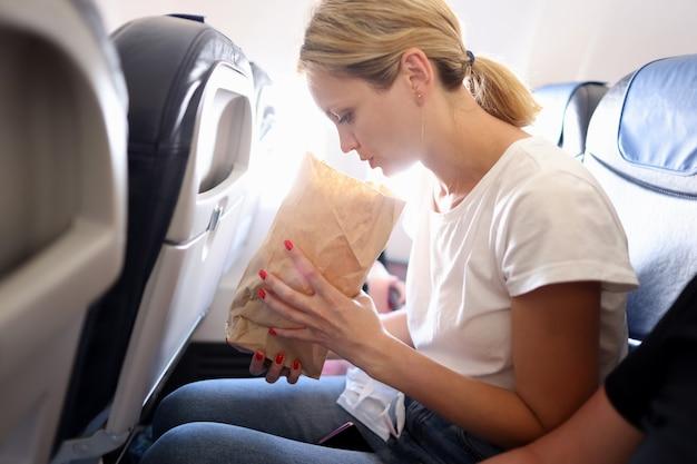Молодая женщина летит в самолете и дышит в бумажный пакет