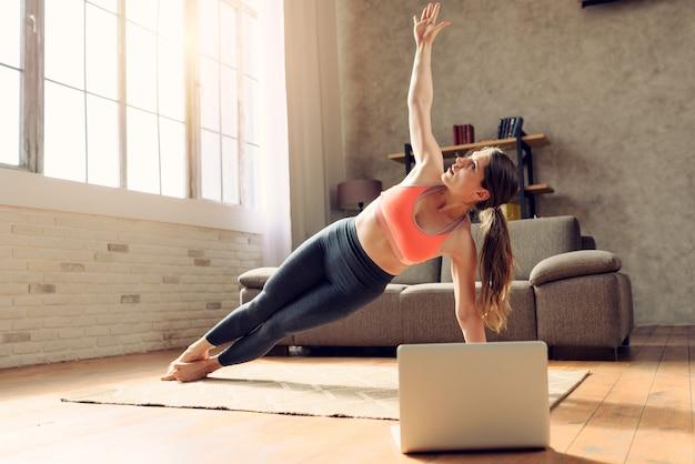 젊은 여자는 체육관 운동 노트북과 함께 다음과 같습니다. 그녀는 코로나 바이러스 codiv-19 격리로 인해 집에 있습니다.