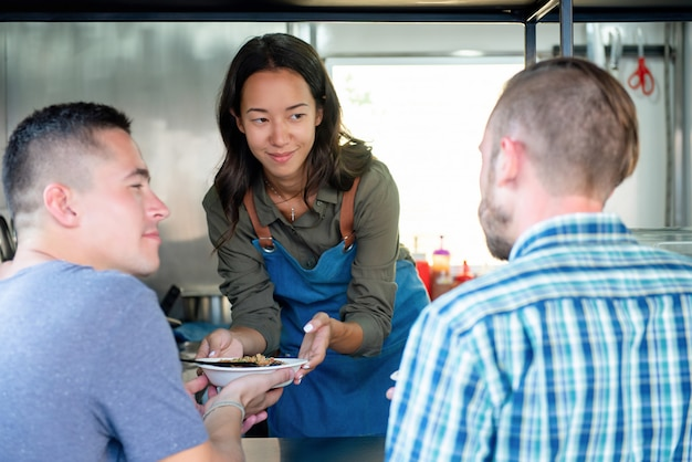 Young woman food truck business owner serving food to a customer