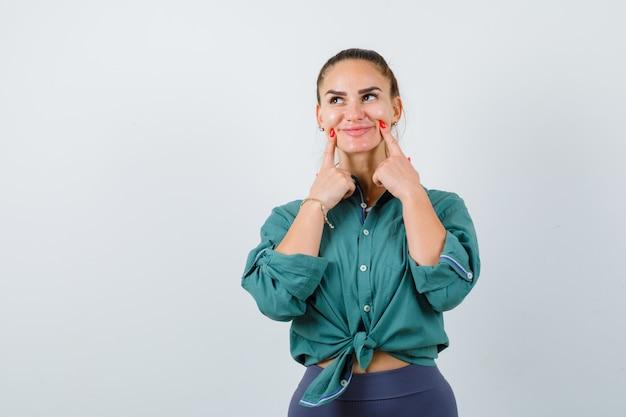 Молодая женщина заставляет улыбаться на лице пальцами, глядя вверх в зеленой рубашке и выглядит веселой, вид спереди.