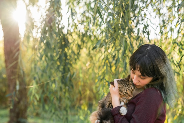Young woman in forest holding her lovely tabby cat