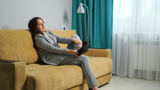 Young woman in a formal suit sits down on the sofa taking off shoes. foot massage, feet swelling.