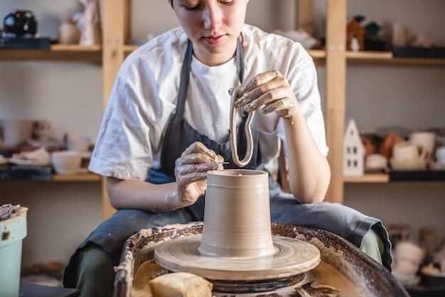 Молодая женщина, формируя глину своими руками, создавая кувшин в мастерской.