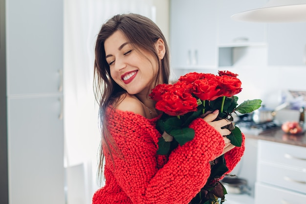 Young woman found bouquet of roses on kitchen. happy girl holding and hugging flowers. valentines day surprise