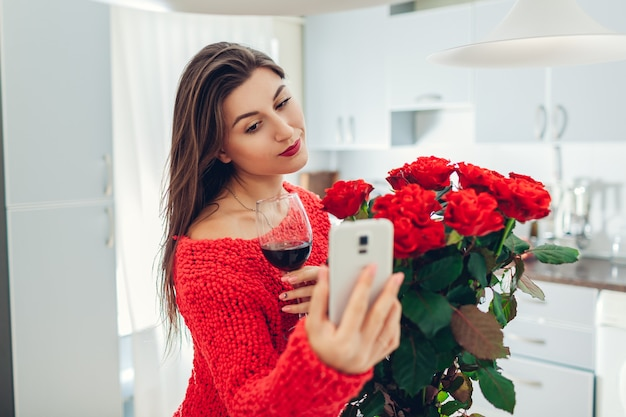 Young woman found bouquet of roses on kitchen. happy girl taking selfie on phone drinking wine. valentines day surprise