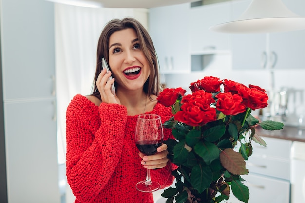 Young woman found bouquet of roses on kitchen. happy girl talking by phone and drinking wine. valentines day surprise