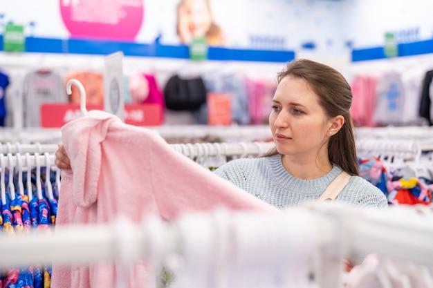 젊은 여성이 아동복 매장에서 자녀에게 적합한 복장을 찾았습니다.