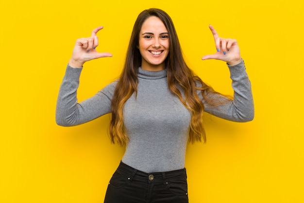 Young woman framing or outlining own smile with both hands, looking positive and happy, wellness concept job or business concept