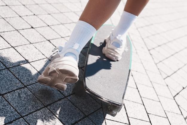 Roのスケートボードに乗って通りの若い女性のフリースタイル