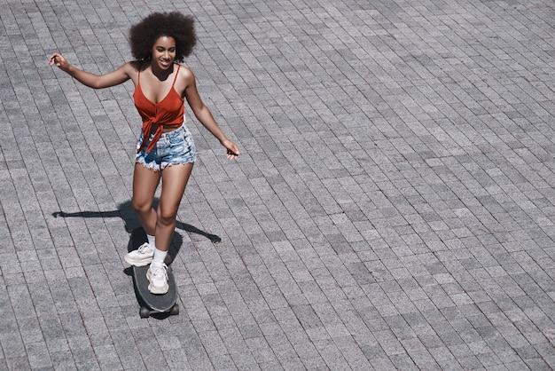 Молодая женщина свободный стиль на улице катается на скейтборде на ро
