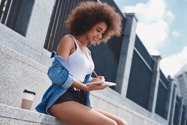 Молодая женщина в свободном стиле на улице, сидя на лестнице с чашкой