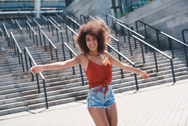 Молодая женщина свободный стиль на улице гуляет возле лестницы вручает