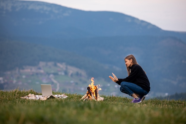 Young woman freelancer sits by the fire and warms his hands in the mountains in the evening. tourist girl resting and working on laptop outdoor