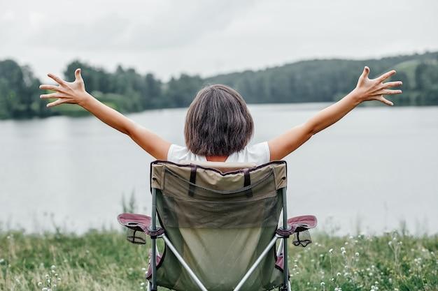 젊은 여자 프리랜서 의자에 앉아 호수 근처 자연 속에서 휴식. 여름철 야외 활동. 국립 공원에서 여행하는 모험. 레저, 휴가, 휴식