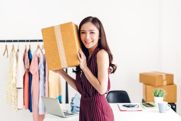 Молодая женщина-фрилансер малого бизнеса онлайн-шоппинг с картонной коробкой на столе дома