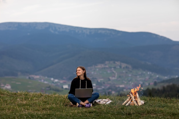 Young woman freelancer with laptop in the mountains in the evening. tourist girl sitting near campfire.
