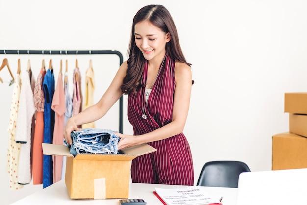 Молодая женщина фрилансер, работающая в сфере бизнеса, покупок и упаковки одежды с картонной коробкой на дому