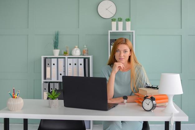 젊은 여성 프리랜서는 노트북 온라인 학습을 위해 집에서 일합니다