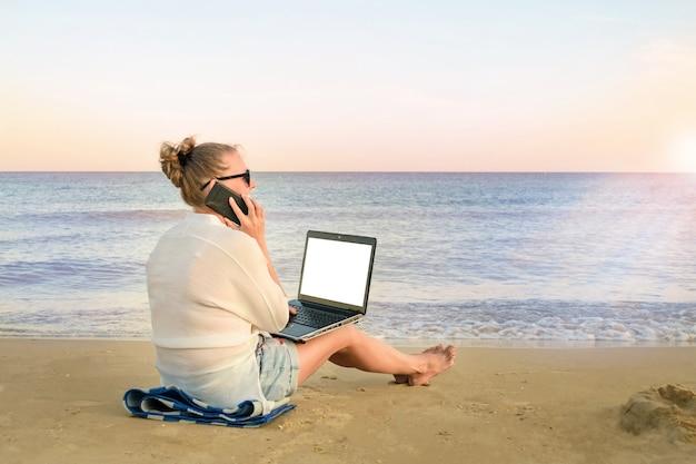 Молодая женщина-фрилансер работает на берегу моря. женщина разговаривает по мобильному телефону, с портативным компьютером в руках, на пляже.