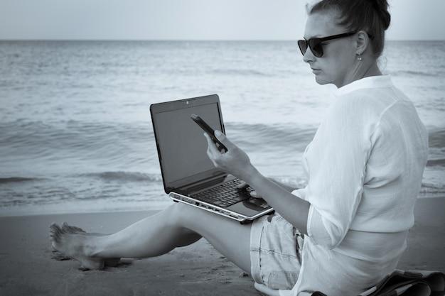 Молодая женщина-фрилансер работает на берегу моря. женщина с портативным компьютером на пляже, черно-белое фото. внештатная работа, отпуск