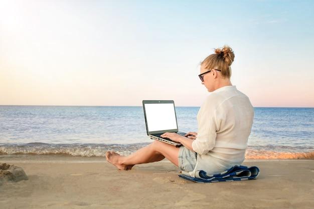 Молодая женщина-фрилансер работает на берегу моря. женщина с портативным компьютером на пляже.