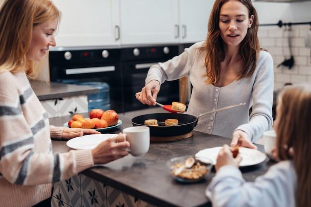 Молодая женщина жарит творожные лепешки или сырники и угощает гостей.