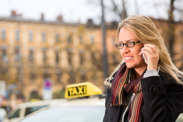 Young woman in front of taxi with phone