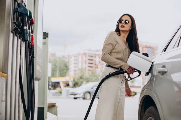 Молодая женщина заправляет свою машину