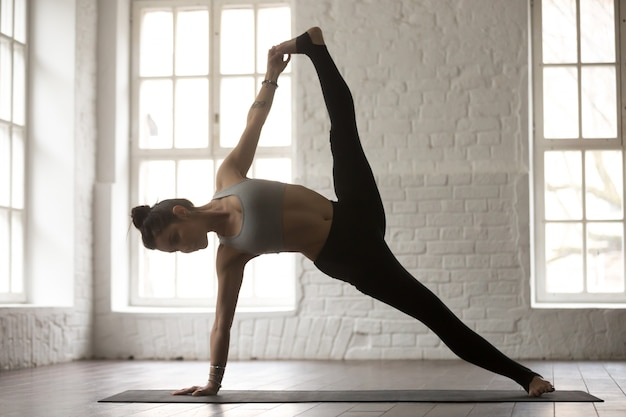 Young woman in full version of vasisthasana pose