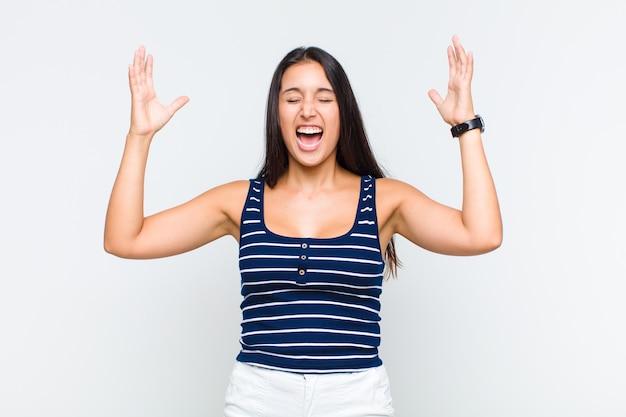 若い女性が猛烈に叫び、ストレスを感じ、空中で手を上げてイライラし、なぜ私が