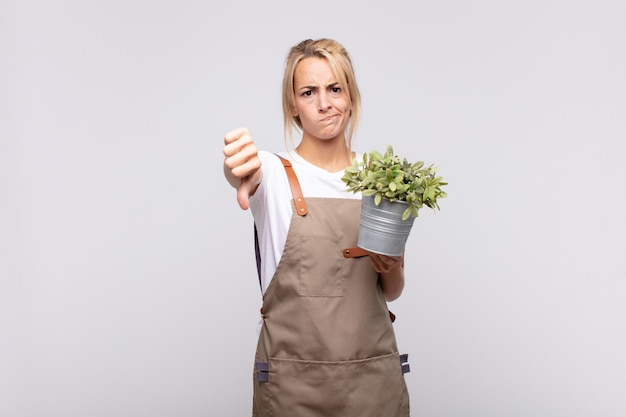 Young woman gardener feeling cross, angry, annoyed, disappointed or displeased, showing thumbs down with a serious look