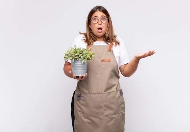 Молодая женщина-садовник чувствует себя чрезвычайно шокированной и удивленной, встревоженной и панической, с напряженным и испуганным взглядом.