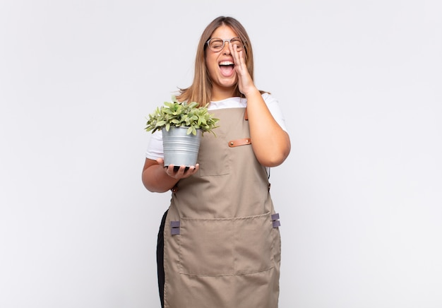 Young woman gardener feeling happy, excited and positive, giving a big shout out with hands next to mouth, calling out