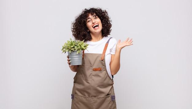 행복, 흥분, 놀라움 또는 충격을 느끼고, 웃고, 믿을 수없는 것에 놀란 젊은 여성 정원사
