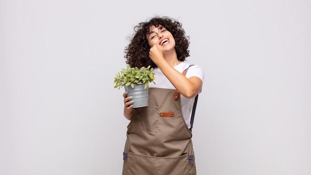 젊은 여성 정원사는 도전에 직면하거나 좋은 결과를 축하 할 때 행복하고 긍정적이며 성공하며 동기 부여