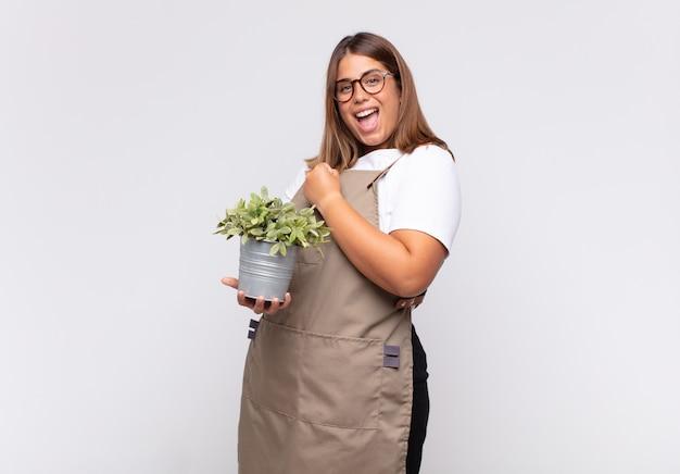 젊은 여성 정원사는 도전에 직면하거나 좋은 결과를 축하할 때 행복하고 긍정적이며 성공하며 동기를 부여받습니다.