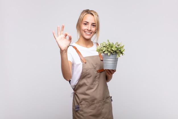 젊은 여자 정원사는 행복하고 편안하고 만족감을 느끼고, 괜찮은 제스처로 승인을 보여주는 미소