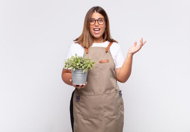 행복하고 놀란 쾌활한 느낌, 긍정적 인 태도로 웃고, 해결책이나 아이디어를 실현하는 젊은 여성 정원사