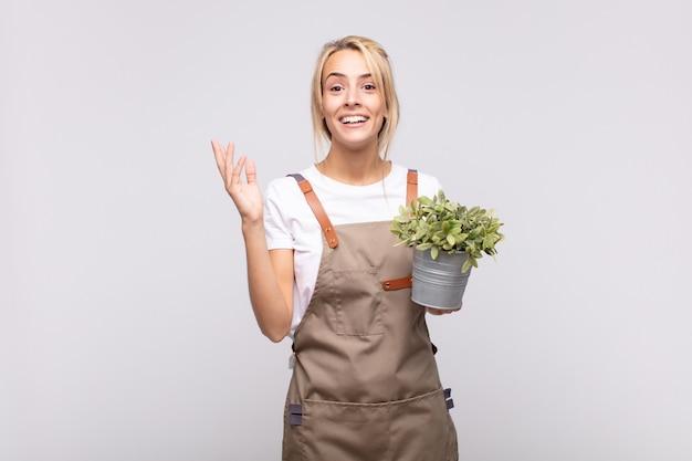 젊은 여성 정원사는 행복하고, 놀라고, 쾌활하며, 긍정적인 태도로 웃고, 해결책이나 아이디어를 깨닫습니다.